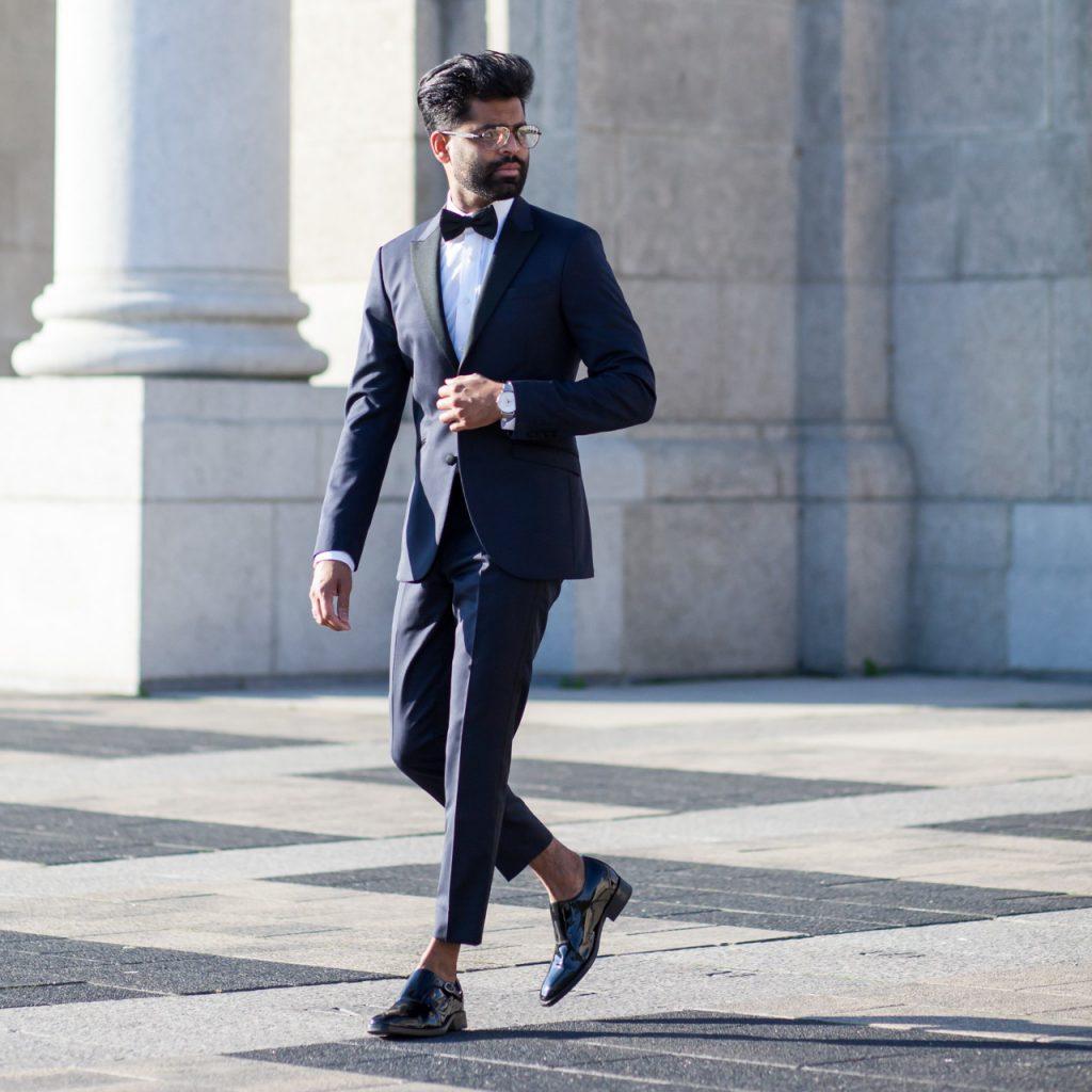 short man wearing shiny black monk dress shoes