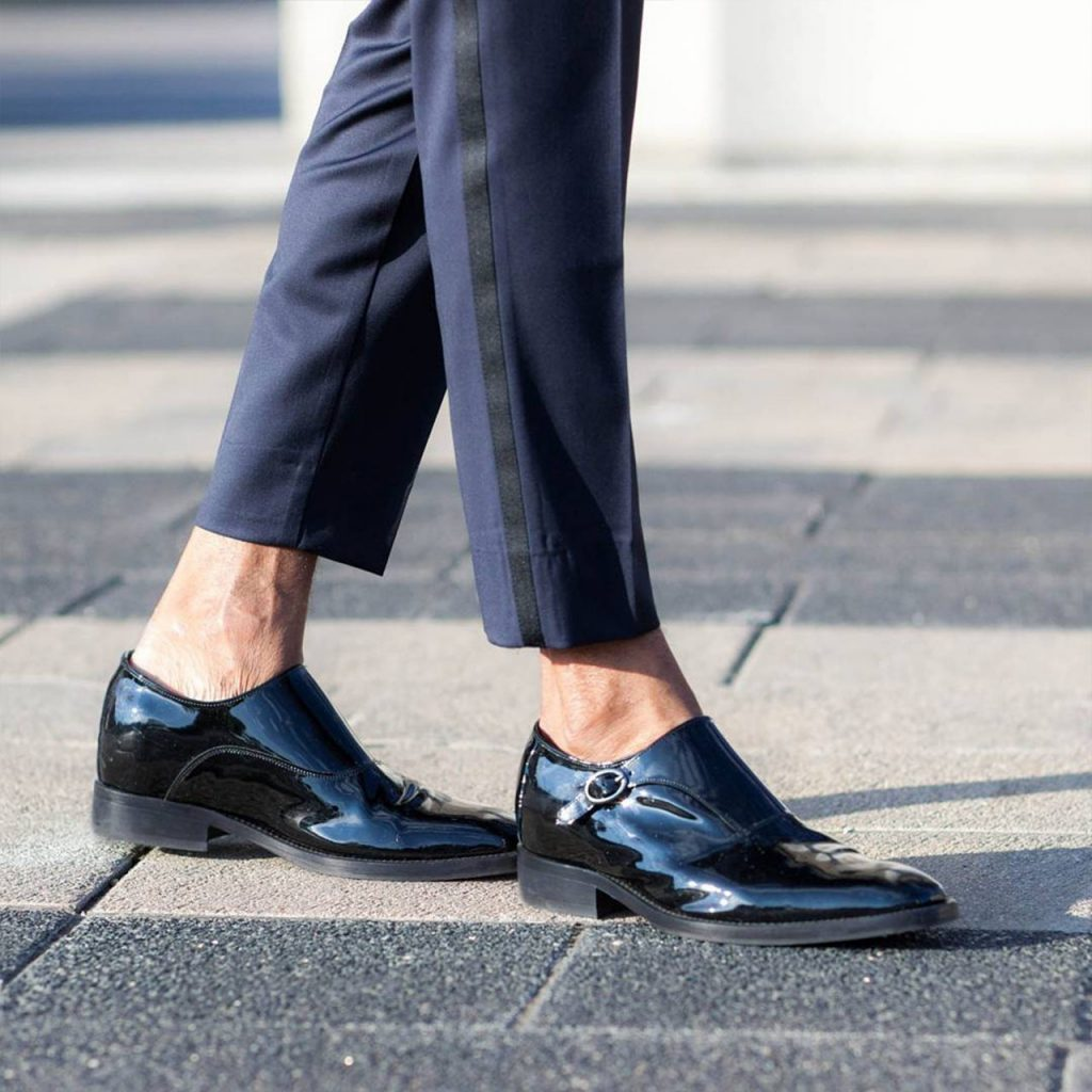 man wearing shiny black monk dress shoes