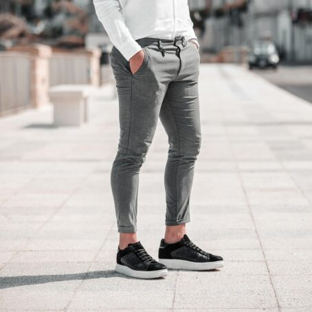man wearing black waxed suede sneakers with textured leather on side