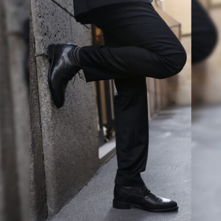 man wearing black leather derby shoes with brogue decoration 7