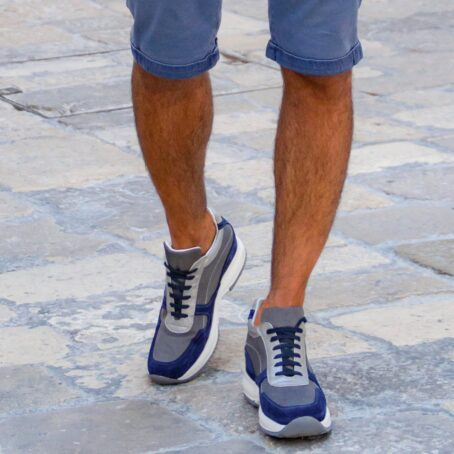 Man wearing blue and grey sneakers